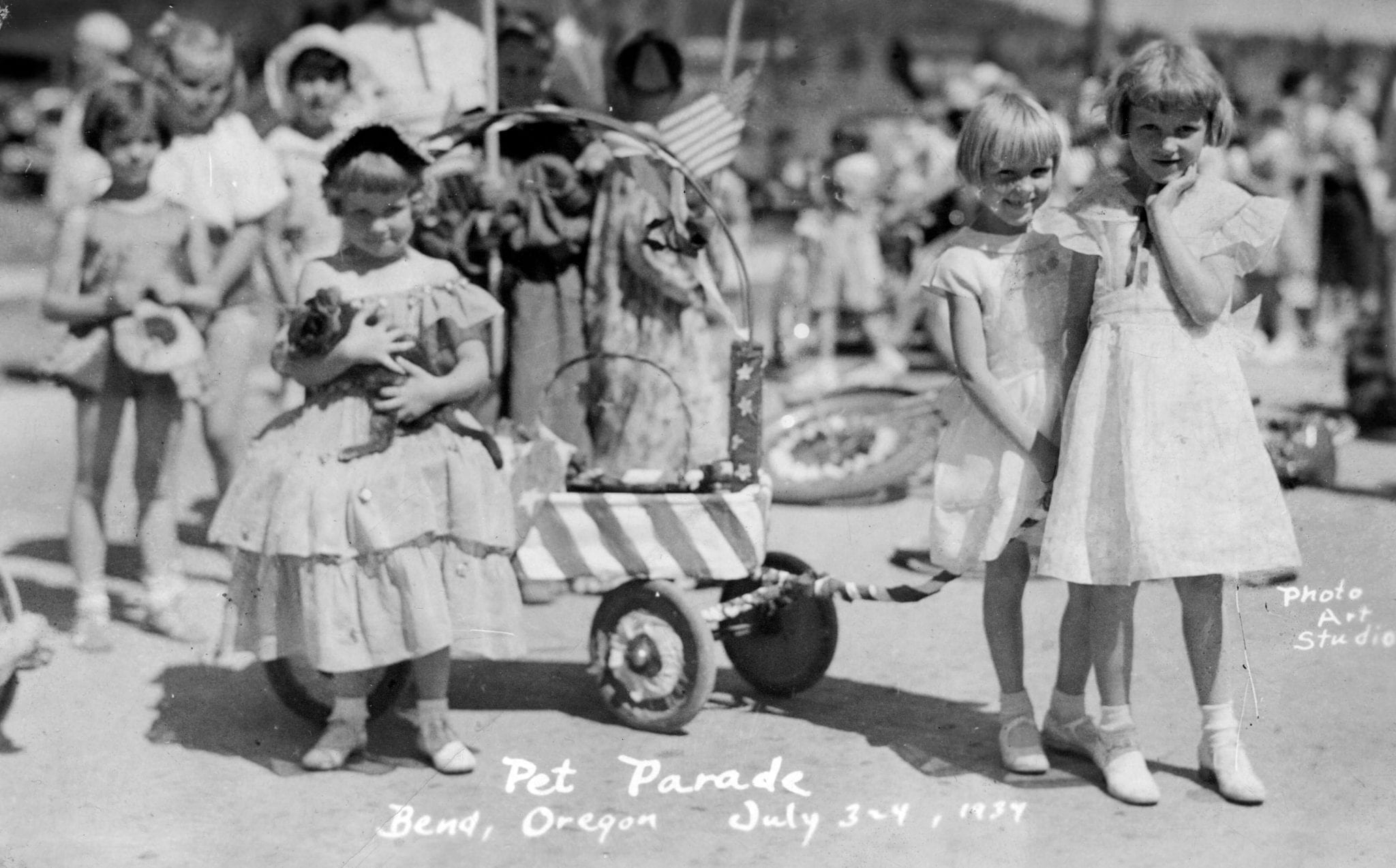 Genevieve Armstrong (with cat) and sister Joyce in the 1934 pet parade. Friend Elma Ramlo accompanies, pulling the wagon.
