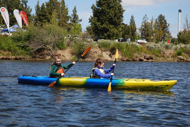 Family kayaking adventure on the Deschutes River in Bend, Oregon.
