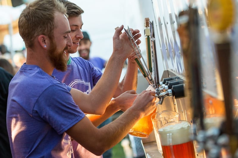 Volunteers pour beer at Bend Brewfest in Bend, Oregon.